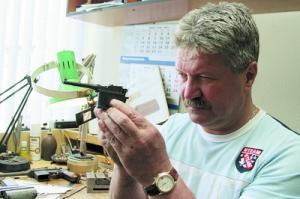 """Мастер Валерий Соснин проверяет прицел миниатюрного """"Маузера"""". Пистолетик отличается от оригинала только размерами - он уменьшен в три раза."""